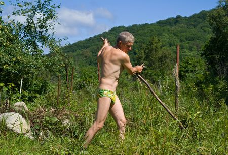 mows: A man mows a grass with a scythe on green meadow. Summer, sunny day Stock Photo