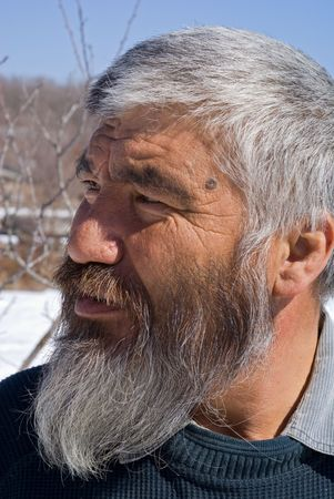 A portrait close-up of the old men with grey beard. Small indigenous people of Russian Far East. Stock Photo