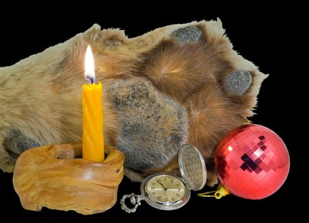 A close up of the paw of tiger, burning candle, watch and red sphere. Symbol of year 2010. Isolated on black. photo