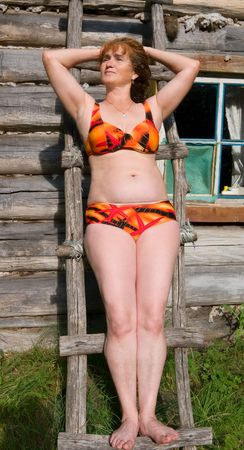 log hair: A woman in bikini stands at log cabin among forest.
