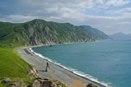 seawater: A landscape on sea: seawater and surf, cliffs and rocks, green capes and cloudy sky. Stock Photo