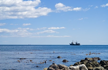 seawater: A landscape on sea. A ship on horizon, cloudy sky, reefs and stones in azure seawater.