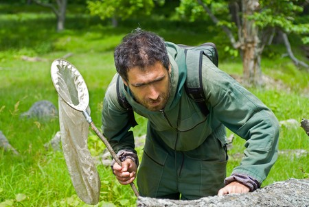 The entomologist with butterfly-net in forest.