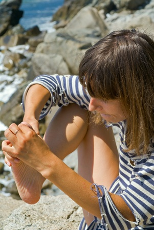 splinter: The young woman pulls out a splinter from a foot. Stock Photo