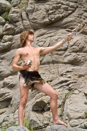 loincloth: The young man in loin-cloth stands at rocks with skull and bone in his hands.