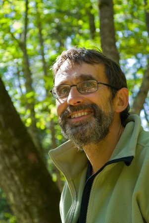 A portrait of the man with beard in glasses.