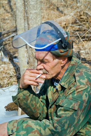 The worker with faceguard smokes in forest. Stock Photo - 11316902