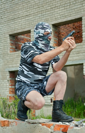 constabulary: A policeman in camouflage mask with pistol. Stock Photo