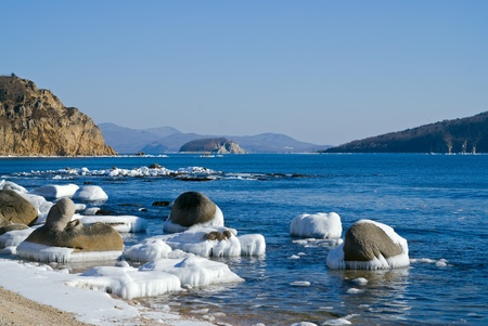 The small island in sea. Winter, stones and ice.
