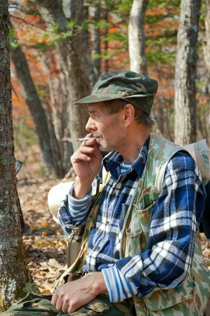 The man sits and smokes in autumn forest. photo