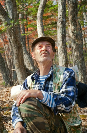 The man sits and relaxes in autumn forest. photo