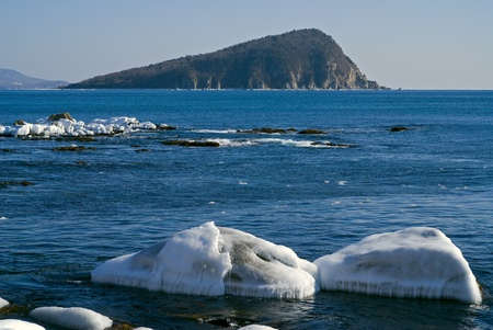 The small island in winter sea, stones and ice.