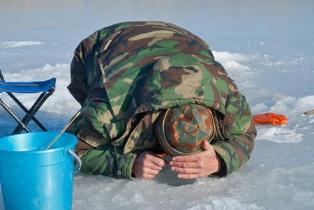 fishing tackle: A man on winter fishing on ice of river. Season of smelt fishing. Stock Photo