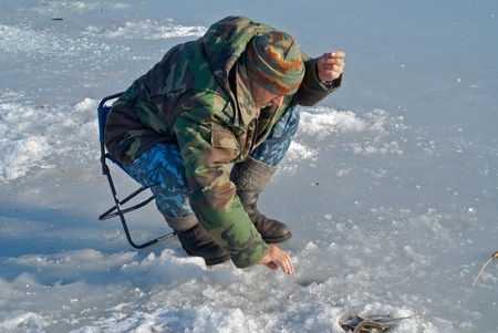 A man on winter fishing on ice of river. Season of smelt fishing. Stock Photo - 12796033