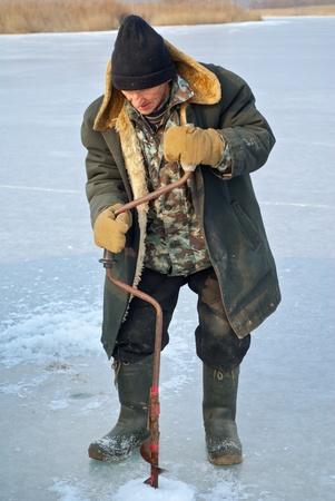 Old man drills ice on winter fishing. Stock Photo