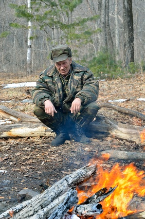 A man at bonfire in forest. Early spring. Stock Photo - 13216761