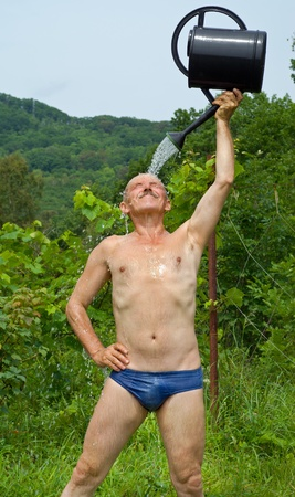 shower man: The man waters himself from a watering can in garden. Stock Photo