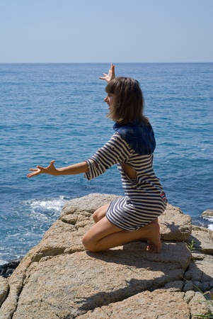The young woman in old striped vest stands on knees on rock at sea.