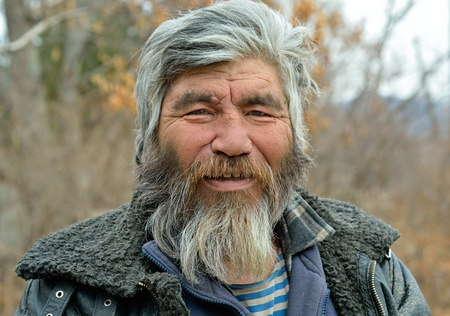 A portrait of the old mongoloid man with grey beard.