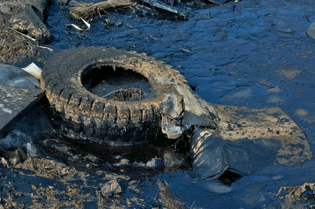 A rubbish heap with black oil pollution. Stock Photo