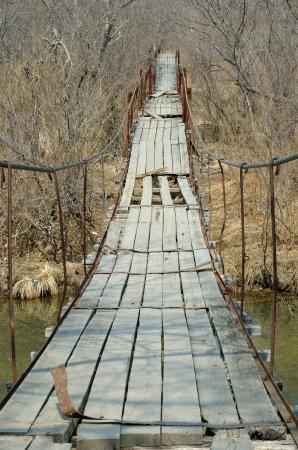 De zeer oude opknoping voetgangersbrug over een kleine rivier.