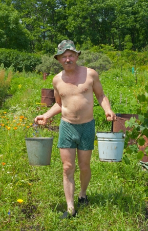 The gardener is carrying a water with buckets. Stock Photo