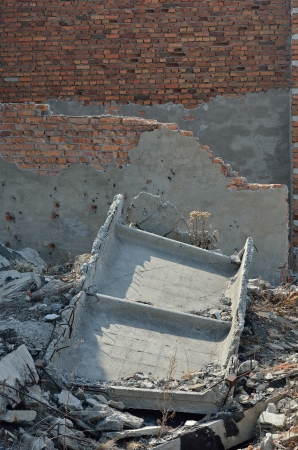 A ruins of building with bullet-holes on wall. photo