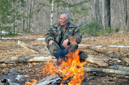 A man at bonfire in forest. Early spring. photo