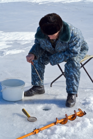 hobbyist: A man on winter fishing on ice of river. Stock Photo