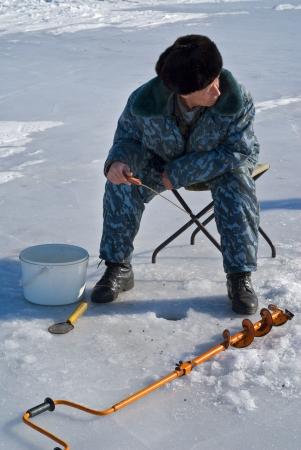handline fishing: A man on winter fishing on ice of river. Stock Photo