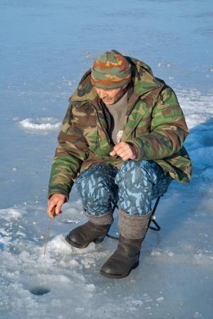 handline fishing: A man on winter fishing on ice of river. Season of smelt fishing. Stock Photo