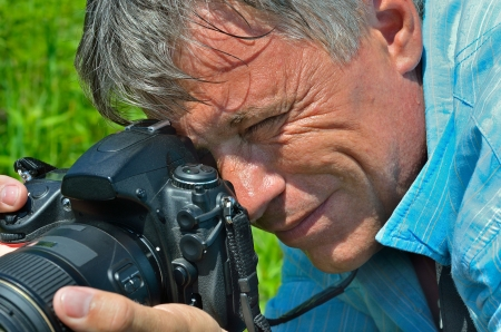 A portrait of the man with camera on nature. Stock Photo - 16061409