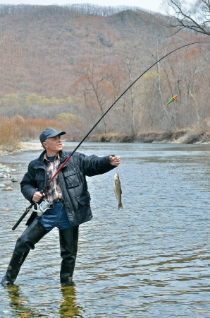 A man on fishing with fish on hook. Stock Photo