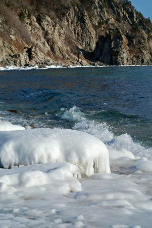 seawater: The landscape on winter sea: stones with ice, seawater and rocks on background.