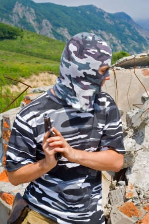 Policeman in camouflage mask with pistol. Stock Photo