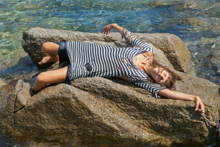 striped vest: The young woman in old striped vest lies on reef in sea