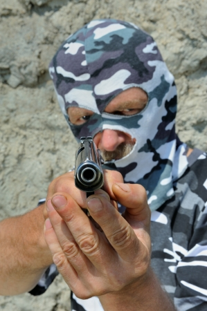 constabulary: Policeman in camouflage mask with pistol. Stock Photo