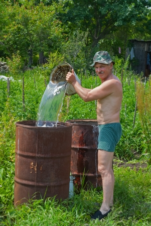 The gardener pours water into a barrel with bucket.