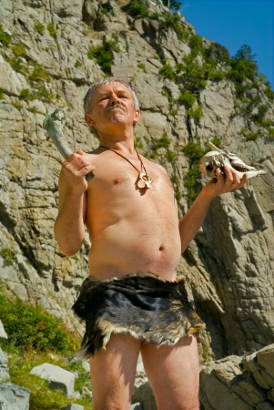 The man in loin-cloth stands at rocks with skull and bone in his hands. Stock Photo