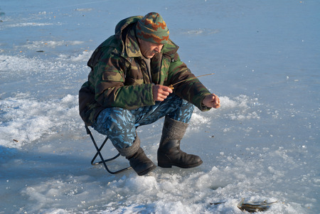 A man on winter fishing on ice of river. Season of smelt fishing. Stock Photo