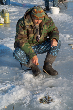 A man on winter fishing on ice of river. Season of smelt fishing. photo