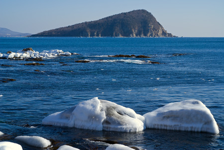 The small island in winter sea, stones and ice. photo