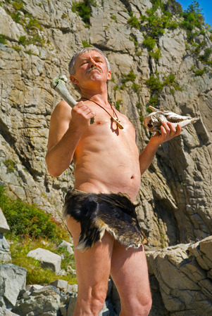 chieftain: The man in loin-cloth stands at rocks with skull and bone in his hands. Stock Photo