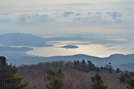 capes: A landscape: taiga on foreground and sea, capes, island, harbor on background.