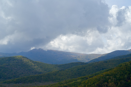 woodsy: The cloudscape in taiga: mountains and cloudy sky. Early autumn.