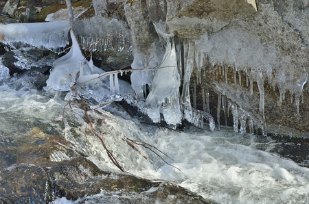 flux: A close up of the icicles and stream on small river.