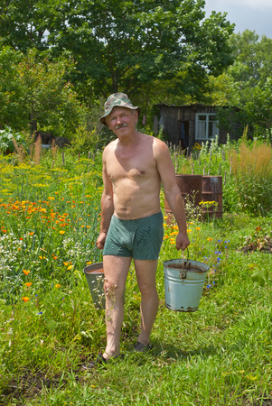drudgery: The gardener is carrying a water with buckets. Stock Photo