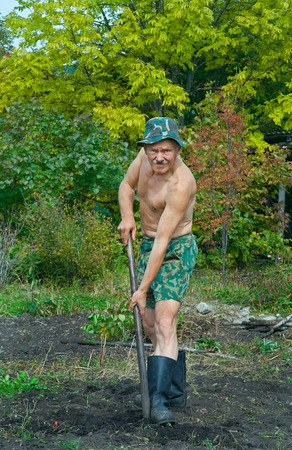 A man on garden digs the ground with spade. photo