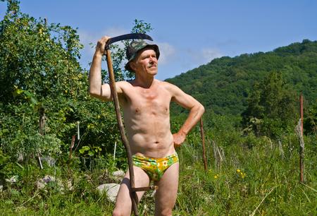 guadaña: Un hombre se coloca con la guadaña en sus manos en la pradera verde. Verano, día soleado. Foto de archivo