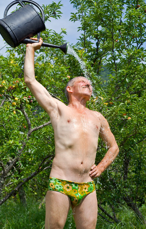 The man waters himself from a watering can in orchard. photo